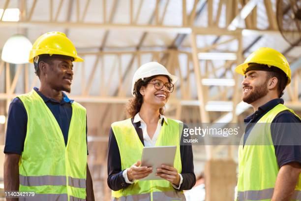 gerente alegre trabajando con trabajadores en fábrica - izusek fotografías e imágenes de stock
