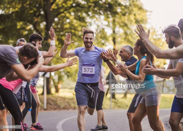cheerful marathon runner greeting group of athletes at finish line. - finishing line stock pictures, royalty-free photos & images