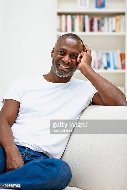 cheerful mature african man sitting o sofa - most handsome black men stock photos and pictures