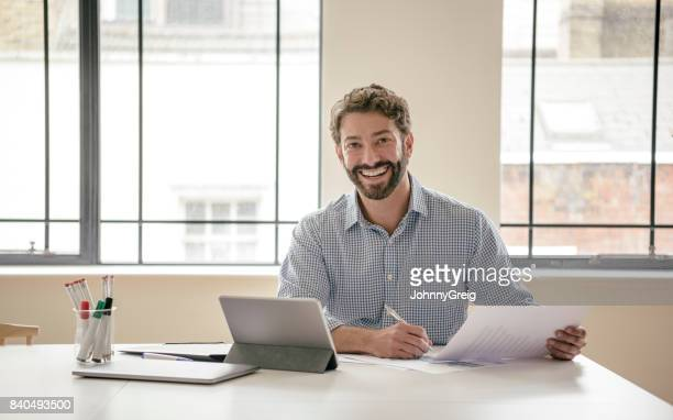 cheerful mature businessman looking at camera and smiling with tablet and document - checked shirt stock photos and pictures