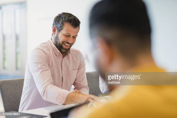 cheerful mature businessman smiling in meeting - office stock pictures, royalty-free photos & images