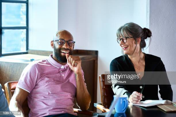 cheerful mature businesswoman laughing with male coworker - compañero de trabajo fotografías e imágenes de stock