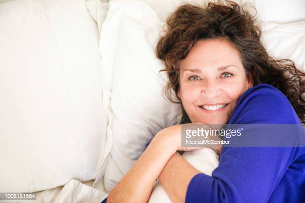 cheerful mature caucasian female portrait in bed hugging her pillow - menopause stock pictures, royalty-free photos & images