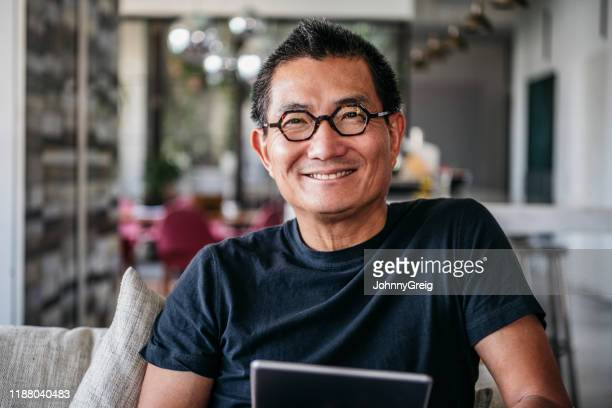cheerful mature chinese man in glasses smiling towards camera - black shirt stock pictures, royalty-free photos & images