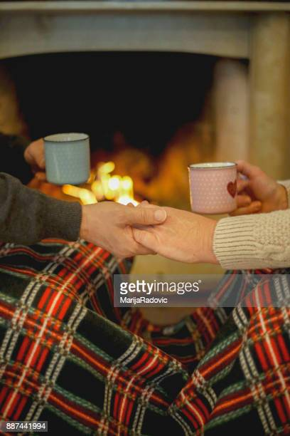 cheerful mature couple celebrating christmas holidays near fireplace - hot love stock pictures, royalty-free photos & images