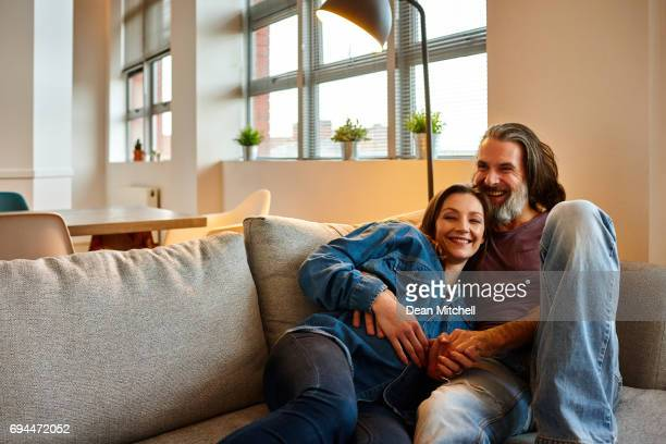 Cheerful mature couple lying together on couch