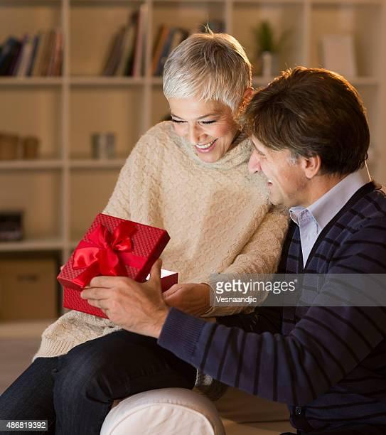 Joyeux couple d'âge mûr ouverture Noël présentent
