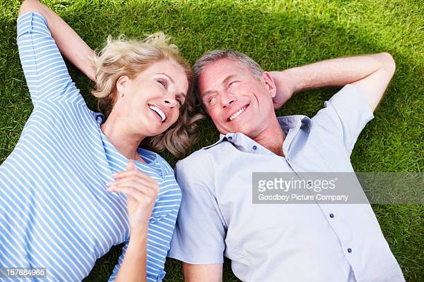 Cheerful mature couple spending time together on grass