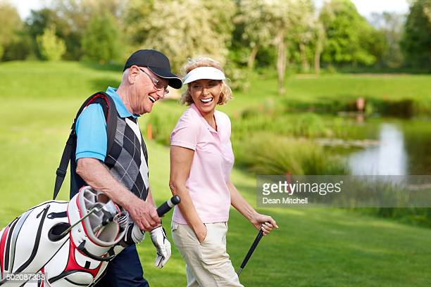 Cheerful mature couple walking on a golf course