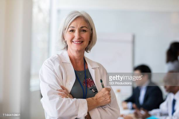 a cheerful mature female doctor stops for a photo - lab coat stock pictures, royalty-free photos & images