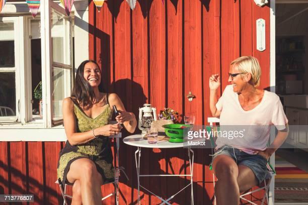 Cheerful mature female friends enjoying summer in back yard on sunny day