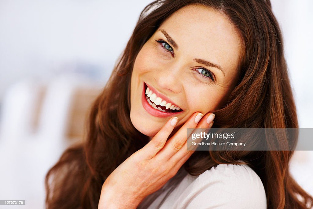 Cheerful mature female with hand on chin : Stock Photo