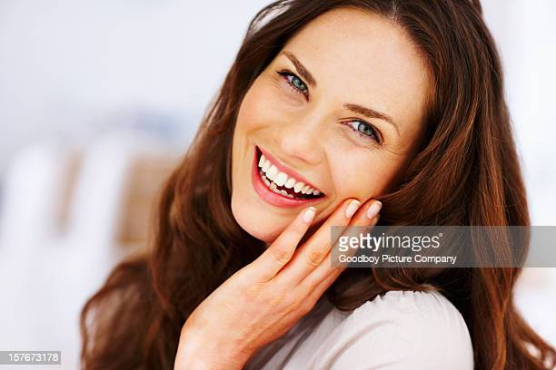 cheerful mature female with hand on chin - brown hair stock pictures, royalty-free photos & images