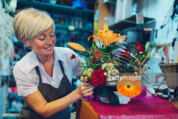 Cheerful mature florist making bouquet in her shop.