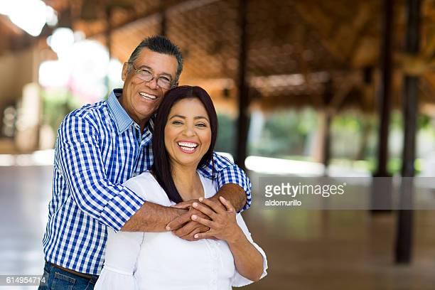 Cheerful mature latin couple looking at camera