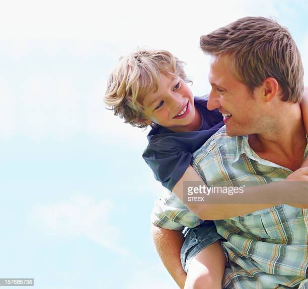 Cheerful mature man carrying his son on back against sky