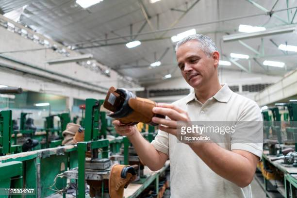 Cheerful mature man checking a boot at a factory very happy