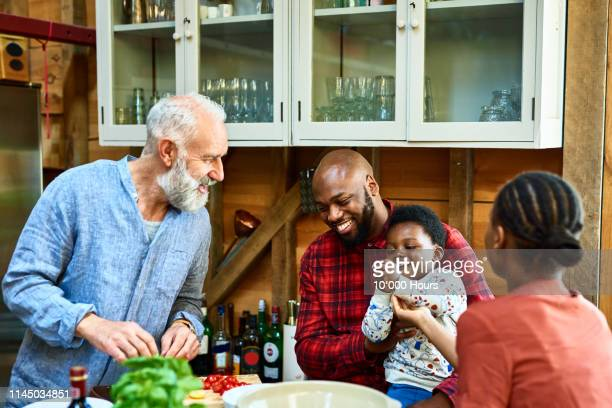 cheerful mature man preparing food family - family and happiness and diverse stock photos and pictures