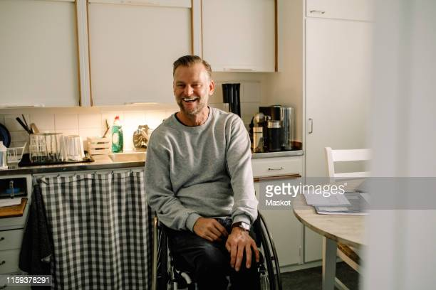 cheerful mature man sitting on wheelchair in kitchen at home - wheelchair stock pictures, royalty-free photos & images