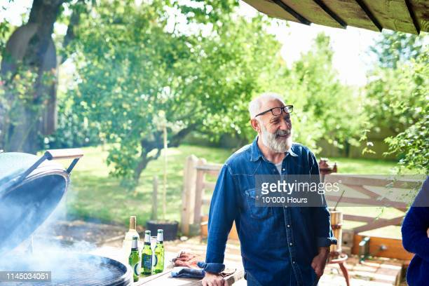 cheerful mature man smiling by bbq in garden - mature men stock pictures, royalty-free photos & images