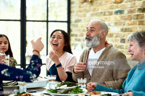 cheerful mature man telling story over dinner with family laughing - family and happiness and diverse stock photos and pictures