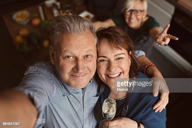 cheerful mature man with arm around woman while taking selfie in kitchen - 50 59 jaar stockfoto's en -beelden