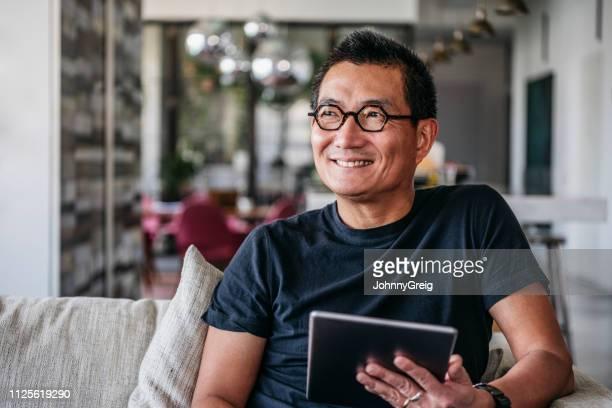 alegre homem maduro com tablet sorrindo e olhando para longe - etnia oriental - fotografias e filmes do acervo