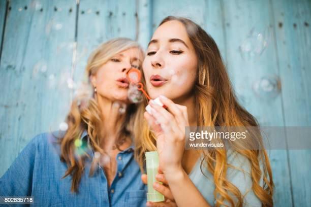 Vrolijke rijpe moeder en jonge dochter bellen blazen
