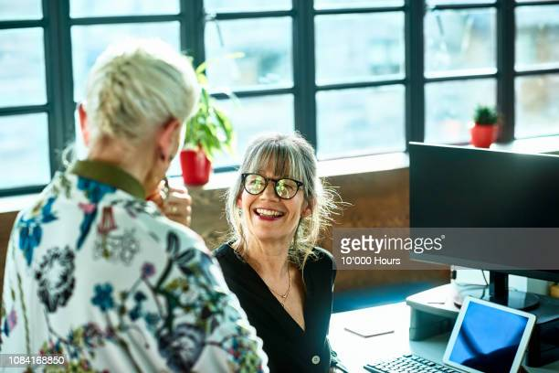 cheerful mature woman at desk smiling towards senior female colleague - manager stock pictures, royalty-free photos & images