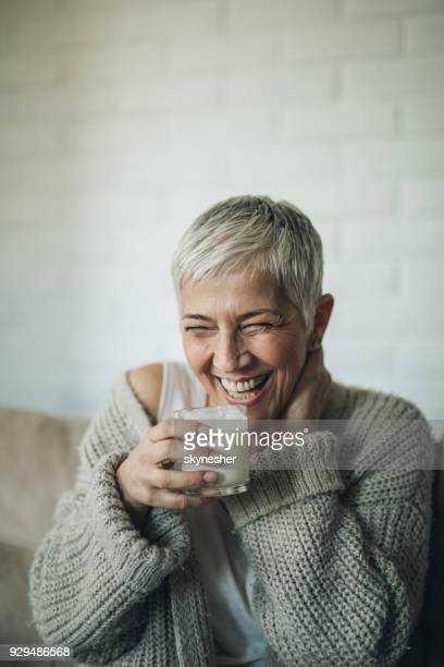 Cheerful mature woman enjoying in glass of milk at home.