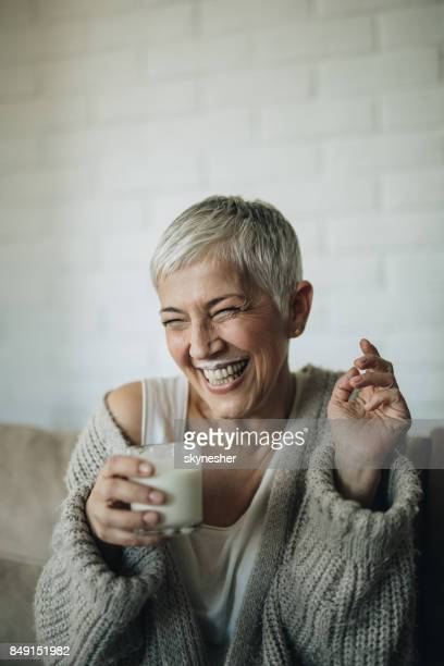 cheerful mature woman having fun while drinking milk. - milk stock pictures, royalty-free photos & images