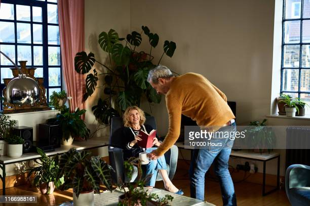 cheerful mature woman reading with husband bringing coffee - mature couple stock pictures, royalty-free photos & images