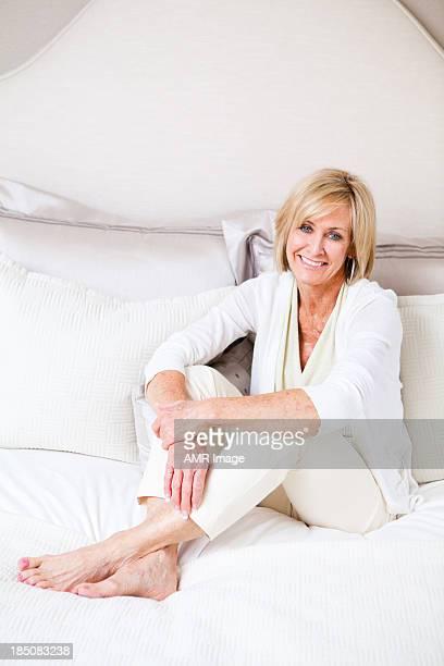 陽気な成熟した女性のベッドでリラックス