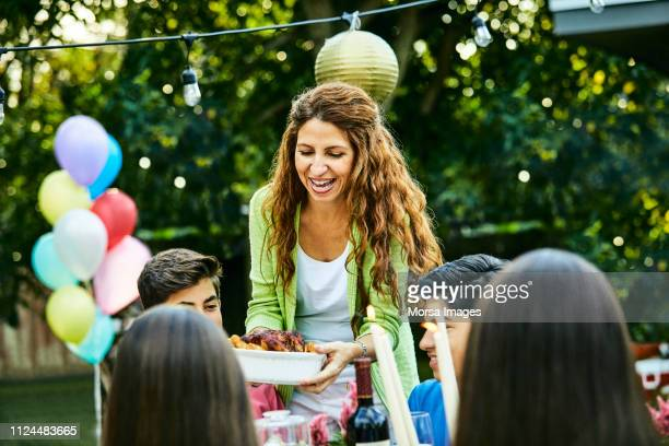 cheerful mature woman serving food to kids - serving food and drinks stock pictures, royalty-free photos & images
