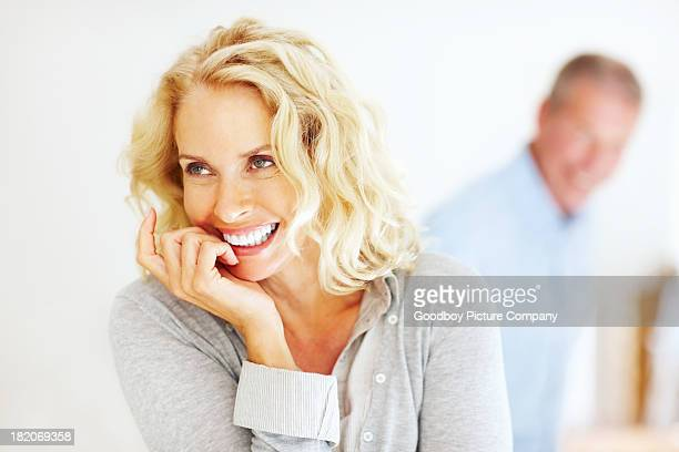 Cheerful mature woman with man in background