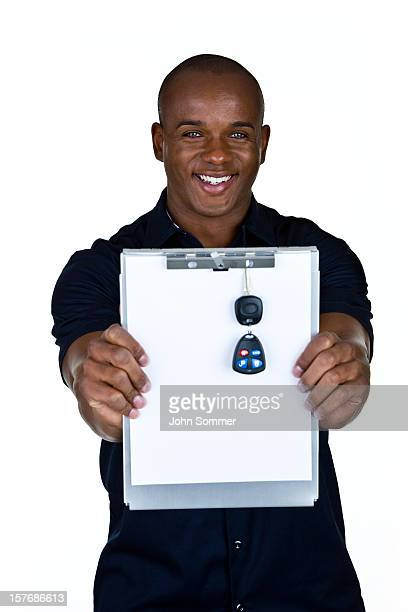 Cheerful mechanic holding up a clipboard with car keys