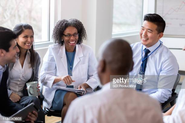 cheerful medical coworkers enjoy staff meeting - medical occupation stock pictures, royalty-free photos & images