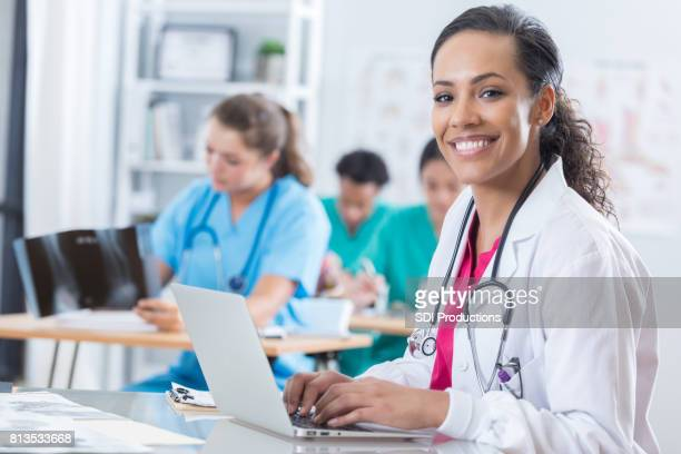 Cheerful medical intern uses a laptop in the classroom