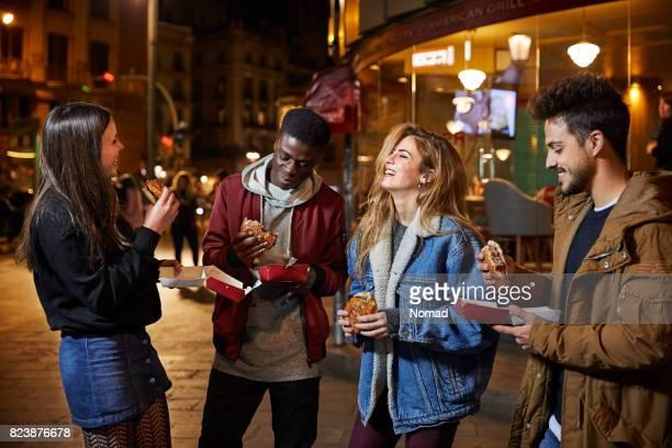 Cheerful men and women having burgers at night