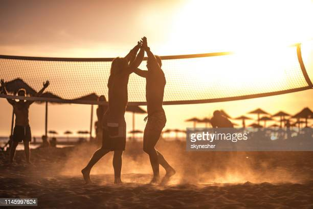 cheerful men celebrating victory in beach volleyball at sunset. - beach volley foto e immagini stock