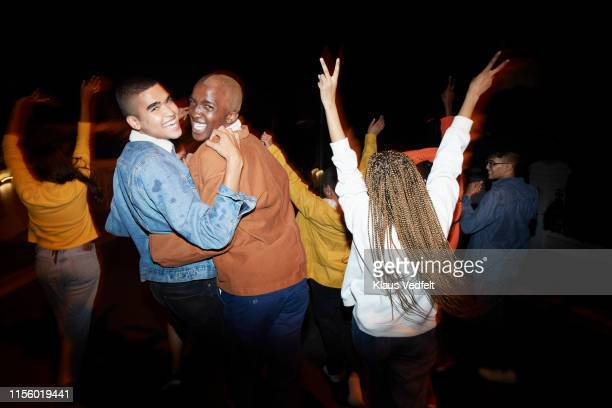 cheerful men dancing with friends at night - lgbtq stock pictures, royalty-free photos & images