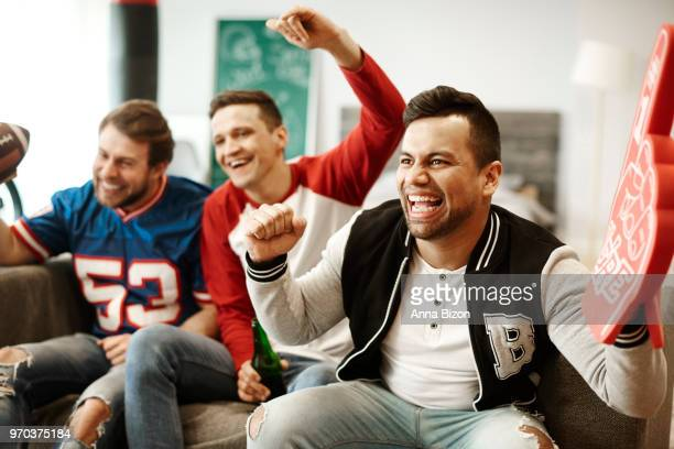 cheerful men supporting their sport team. debica, poland - foam finger stock photos and pictures