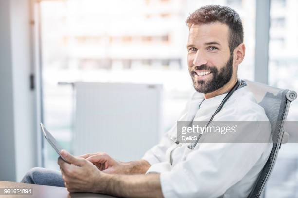 cheerful mid adult male doctor smiling at camera while using tablet. - handsome doctors stock pictures, royalty-free photos & images