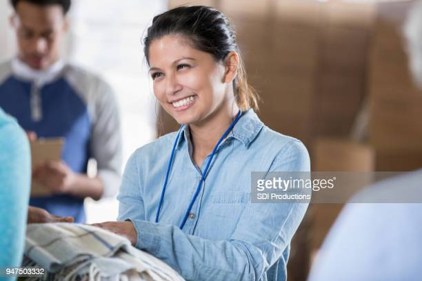cheerful mid adult woman passes out blankets during distaster relief - humanitarian aid stock pictures, royalty-free photos & images