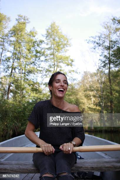 Cheerful Mid Adult Woman Rowing Boat On River In Forest
