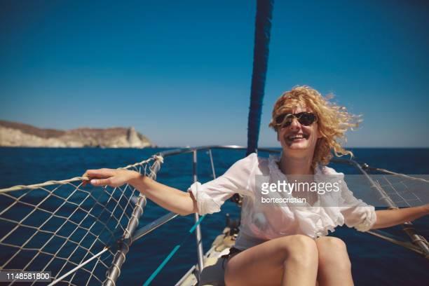 cheerful mid adult woman sitting on sailboat in sea during summer - bortes bildbanksfoton och bilder