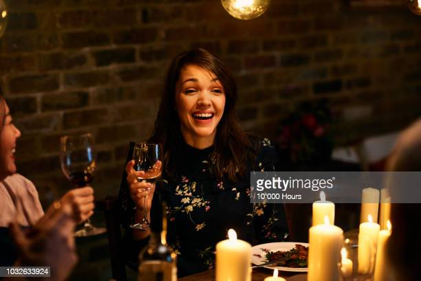 cheerful mid adult woman smiling and holding wine glass at dinner - candlelight stock pictures, royalty-free photos & images