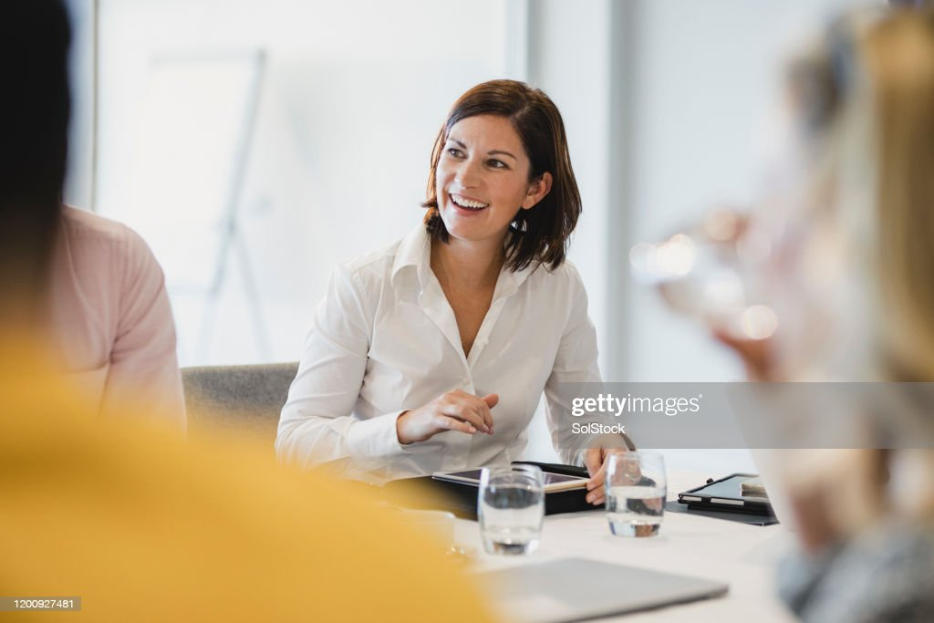 Cheerful mid adult woman smiling at business meeting : Stock Photo