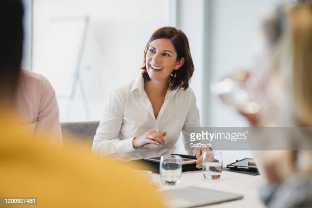 cheerful mid adult woman smiling at business meeting - employee stock pictures, royalty-free photos & images
