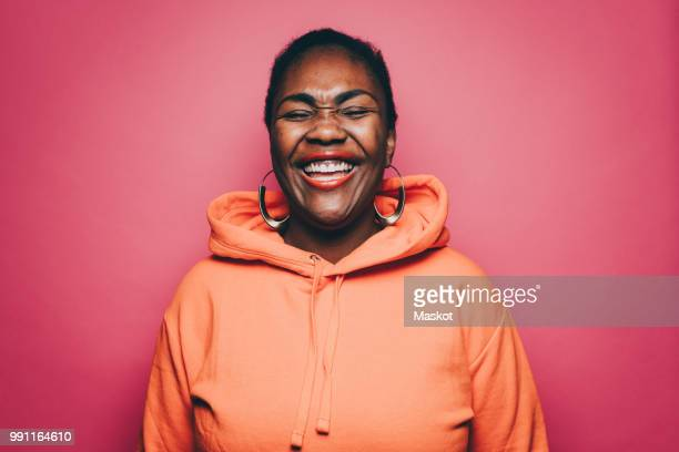 cheerful mid adult woman wearing orange hooded shirt over pink background - hood clothing stock photos and pictures